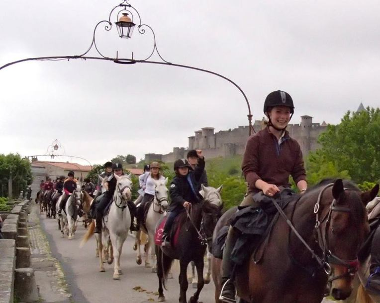 Equiaude Equestrian Parade passing over the Pont Vieux (Old Bridge) with la Cité de Carcassonne in the background.