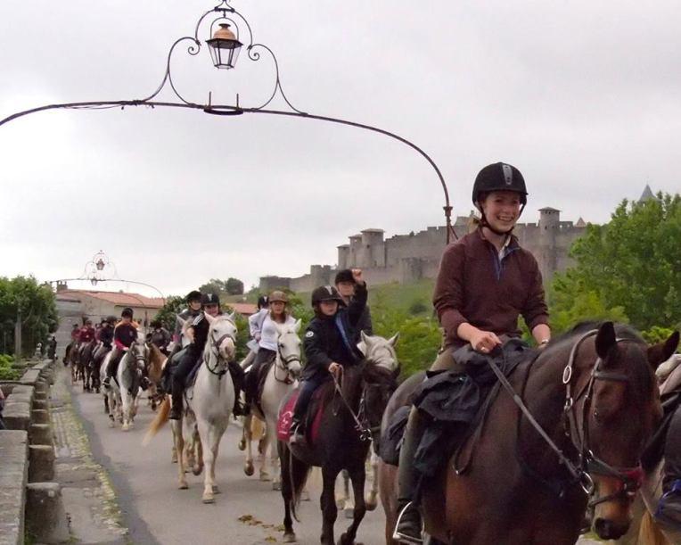 Equiaude Equestrian Parade passing over the Pont Vieux (Old Bridge) with la Cité de Carcassonne in the background.