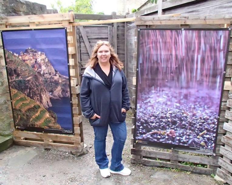 Tracy outside the exhibition with two photos displayed inside. Eighth Annual Terroirs d'Images International Photo Exposition.
