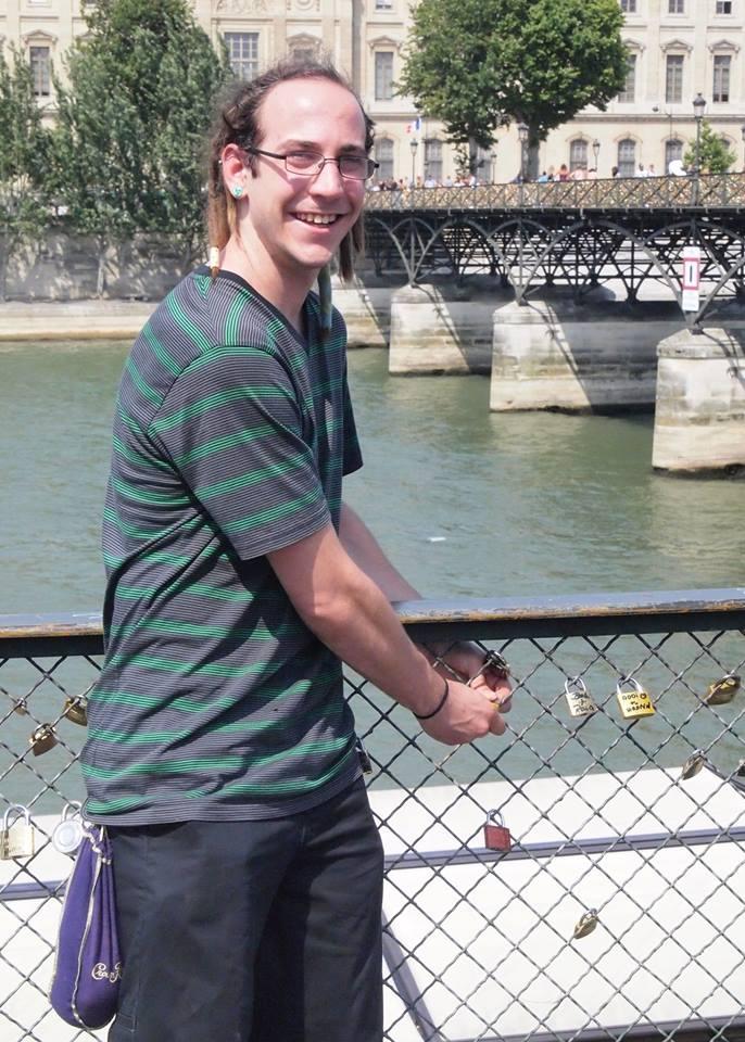Adam putting a lock on the Pont des Arts bridge to memorialize his and Liz's trip to Paris.