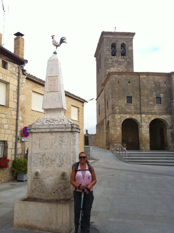 Tracy in Plaza de la Iglesia, Hornillos del Camino, with rooster monument and Iglesia Santa Maria, gothic
