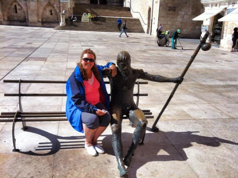 Tracy beside a bronze pilgrim sculpture in Plaza Santa Maria, Burgos