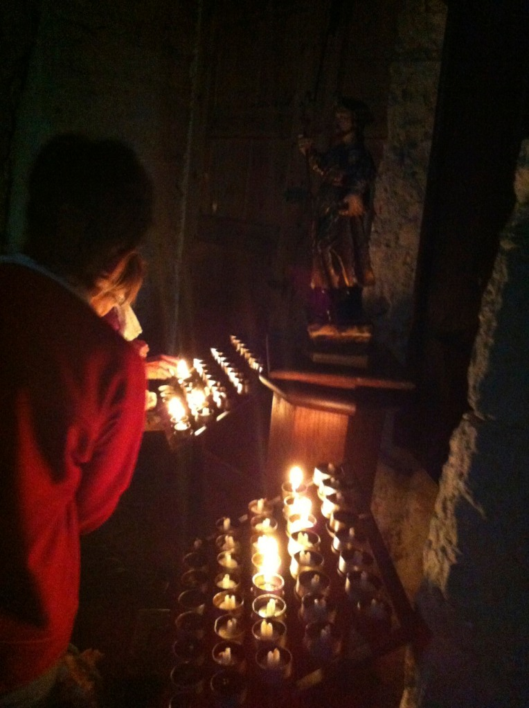 Monk lighting a candle, Iglesia Santa Maria, 12th century, Romanesque, in Rabanal del Camino