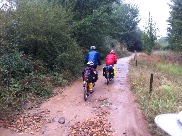 Pedal-grino family of three on muddy trail near Cacabelos