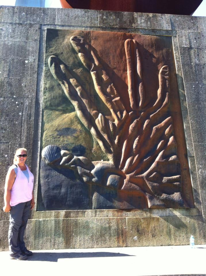 Tracy near panel of Camino routes shaped like a hand at Monte do Gozo, Hill of Joy