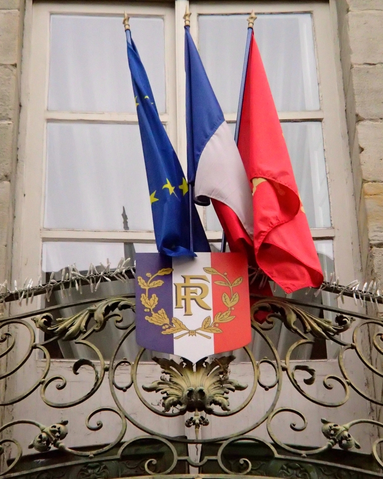 The  flags of the European Union, France, and Languedoc region outside the Mairie (Town Hall.)