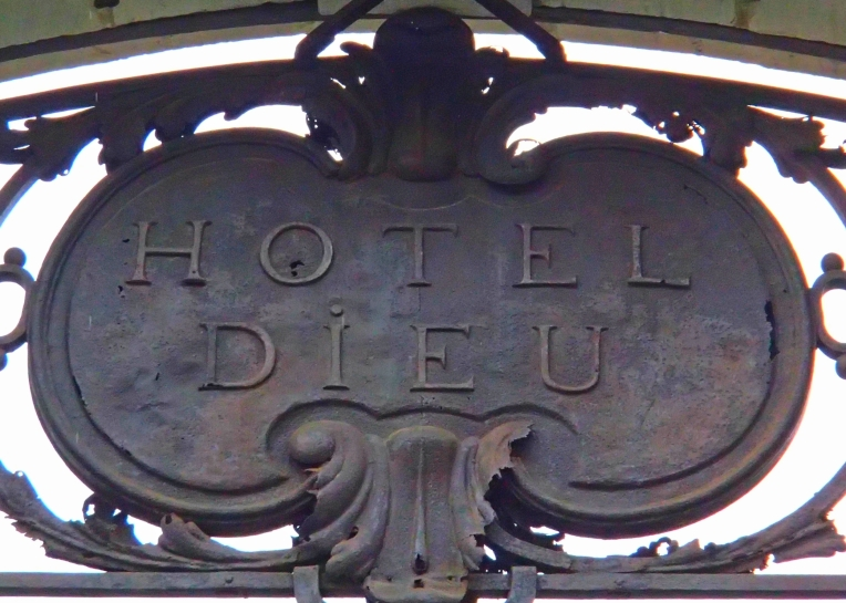 The antique sign above the entrance to the former Hôtel Dieu (God's Hotel)  which was built in 1772 as a city hospital.  The hospital was demolished in 1977 and all that remains today is the entrance gate and Le Dôme, the former bell tower to the hospital's chapel.