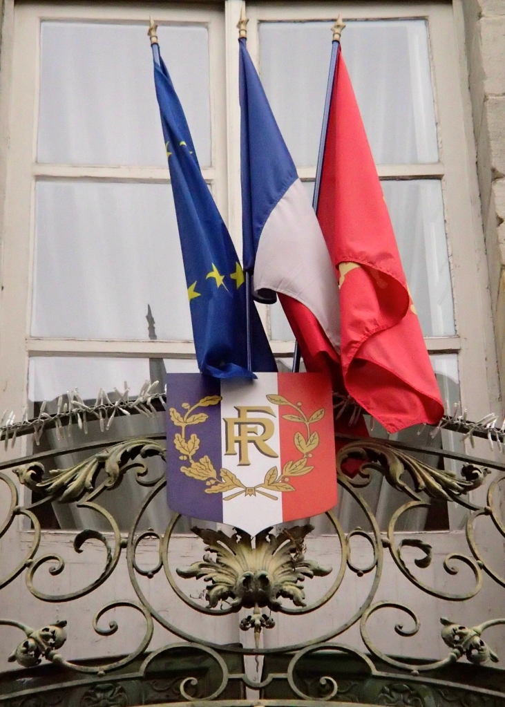 The flags of the European Union, France, and the Languedoc-Roussillon region above the entrance to Hôtel de Rolland, an 18th century hôtel particulier which is now the Mairie (town Hall)  on Rue Aimé Ramond.