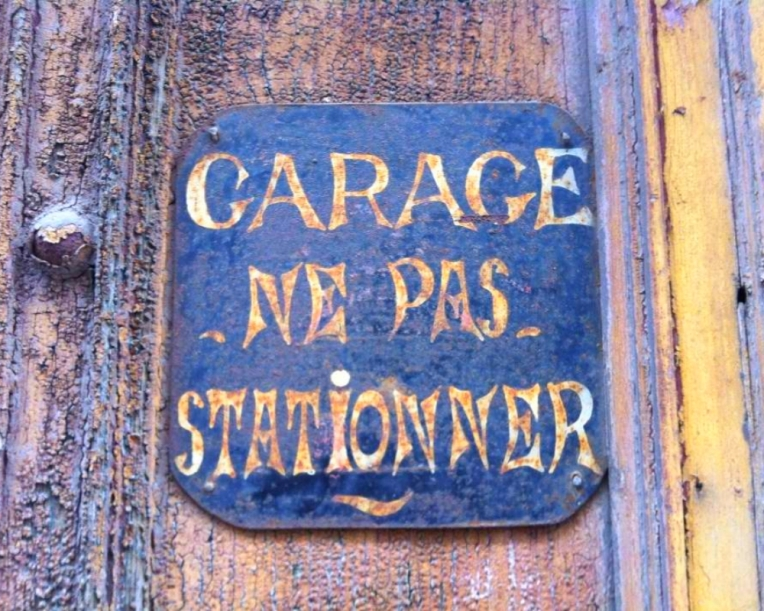 "Antique ""No Parking"" sign on a garage along Rue Jean Bringer."