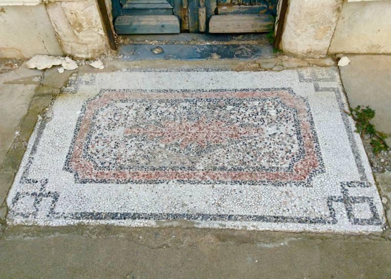 An old mosaic welcome mat.