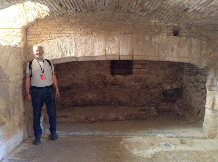 Alan standing beside the huge fireplace in the kitchen.
