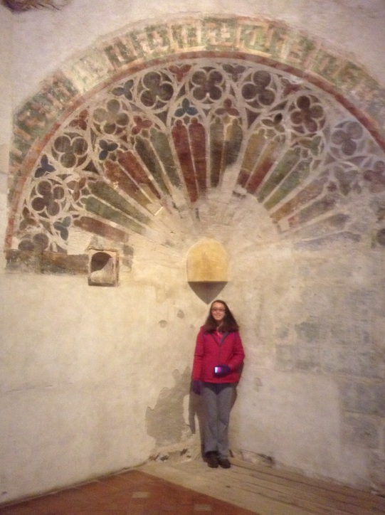 Etta standing under the remains of a geometric fresco in Holy Cross